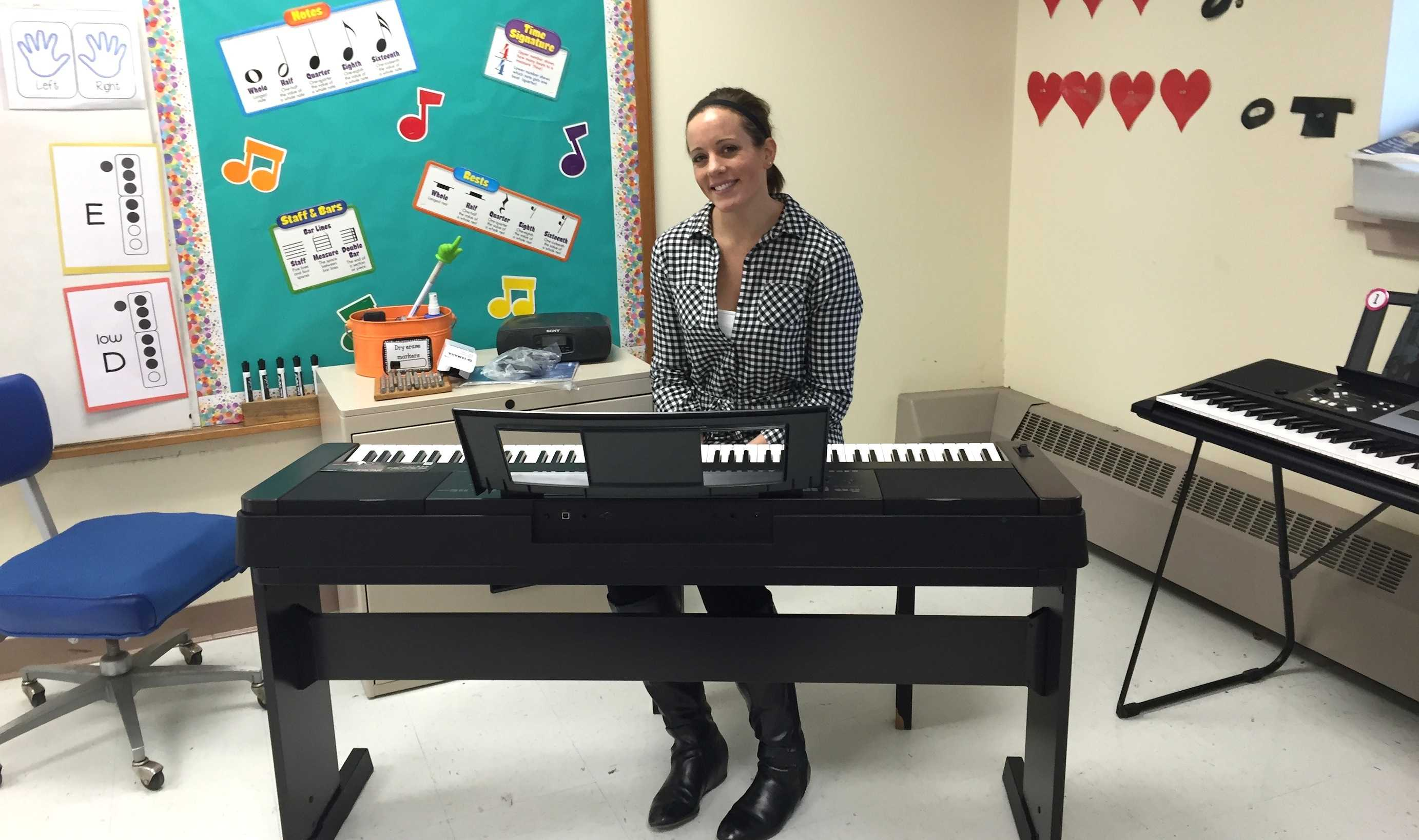 Sara Patashnick -- who teaches music at Hosmer Elementary School in Watertown -- poses with some of the instruments purchased with the recent grant from Music Drives Us.