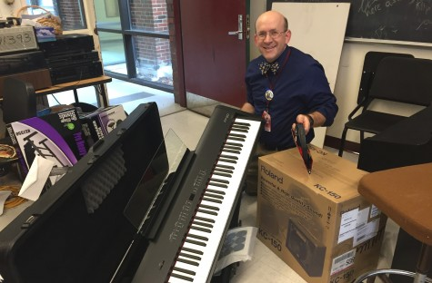 Dan Wulf -- who teaches math, music, and chorus at Watertown High School -- poses with some of the instruments purchased with the recent grant from Music Drives Us.