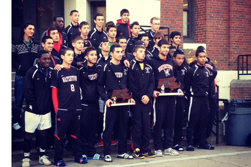 After+arriving+back+at+WHS%2C+the+boys+pose+for+a+team+picture+with+their+North+and+Eastern+Massachusetts+Championship+trophies.