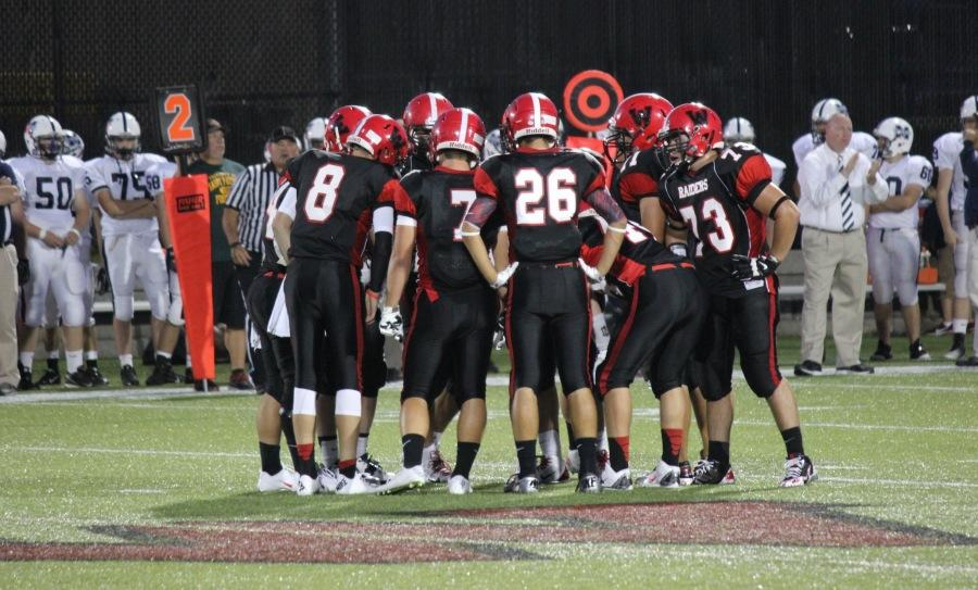 The Raiders huddle up before the start of their first football game of the season, a 21-6 win over Medway on Sept. 12, 2014, at Victory Field.