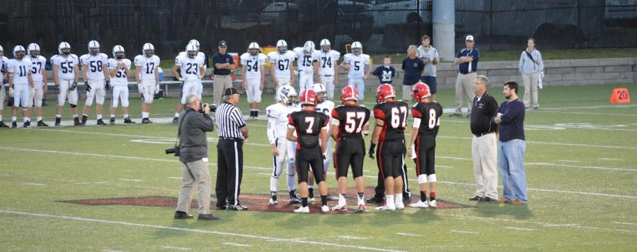 Austin Farry (7), Angel Carrion (57), Erik Baghdasaryan (67), and Nick Giordano meet with Medway's captains before Watertown's season opener begins on Sept. 12, 2014, at Victory Field.