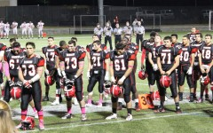 The Watertown High football stands at attention during the playing of the national anthem before the Raiders' Senior Night game at Victory Field with Melrose on Oct. 10, 2014.