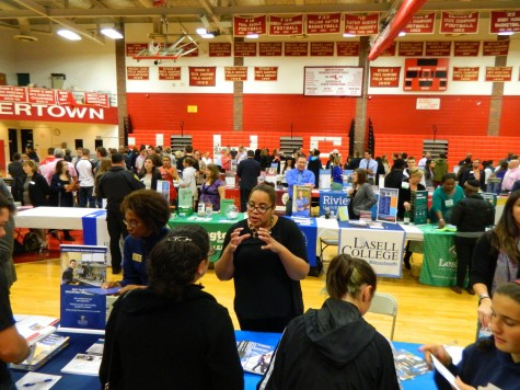 A representative for the Benjamin Franklin Institute of Technology (front, center) talks with a prospective applicant at the annual College Fair at Watertown High School on Oct. 9, 2014.