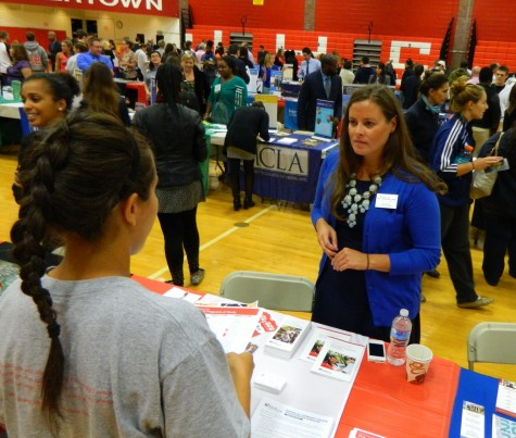 Jill Tyburski from Bunker Hill Community College talks with a prospective applicant at the College Fair at Watertown High School on Oct. 9, 2014.