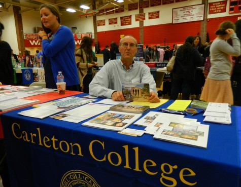 Patrick Field, an alumni rep for Carleton College, works his alma mater's table at the annual College Fair at Watertown High School on Oct. 9, 2014.