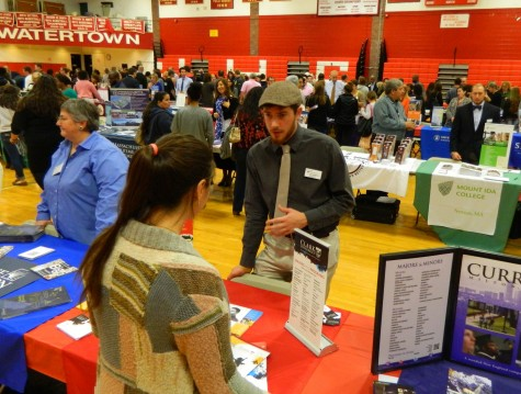 Jake Mattleman, an assistant director of admissions at Clark University, talks with a prospective applicant at the annual College Fair at Watertown High School on Oct. 9, 2014.