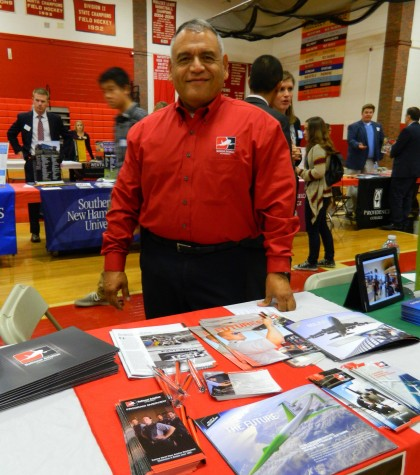 Sam Rath of the National Aviation Academy in Bedford, Mass., stands behind his recruitment materials at the annual College Fair at Watertown High School on Oct. 9, 2014.