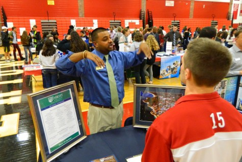 Jameel Moore, assistant director of admission at Endicott College, talks with a prospective applicant at the annual College Fair at Watertown High School on Oct. 9, 2014.