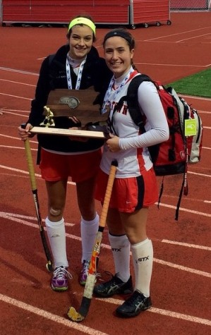 Watertown High cocaptains Allie Doggett (left) and Emily Loprete pose with the Division 2 trophy after the Raider defeated Auburn, 5-0, on Sunday, Nov. 16, 2014, for the state title. Doggett, Loprete, and their senior classmates completed their WHS field hockey careers without ever suffering a loss.