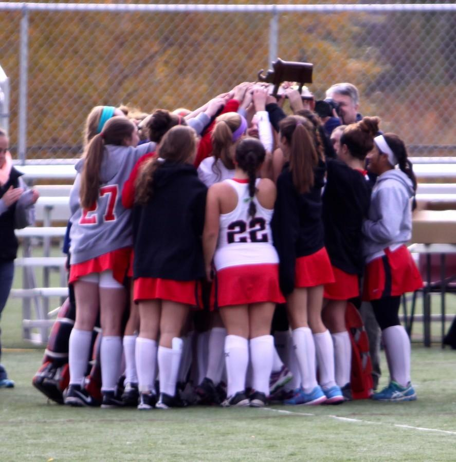Watertown's field hockey team crowds around the Div. 2 North sectional trophy after beating Weston, 2-0, on Nov. 9, 2014. Watertown advanced to the state semifinal on Tuesday, Nov. 11, 2014.