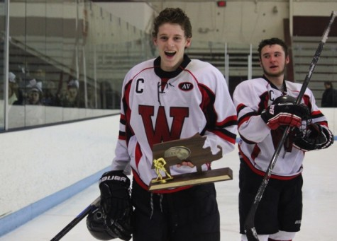 Nick Giordano gets his turn with the Division 3 North trophy as senior classmate Austin Farry looks on after Watertown High's 2-1 victory over Bedford at Chelmsford Arena in Billerica on Friday, March 6, 2015.