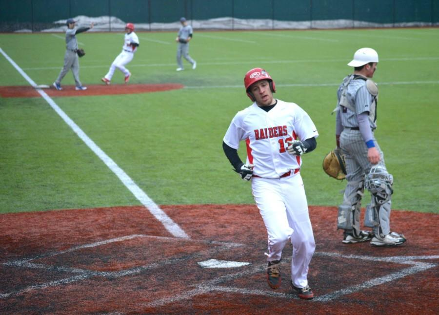Watertown High's Andrew Massarotti scores the Raiders' first run of the 2015 on Greg Yeghishyan triple in the fourth inning Tuesday, April 7, 2015.