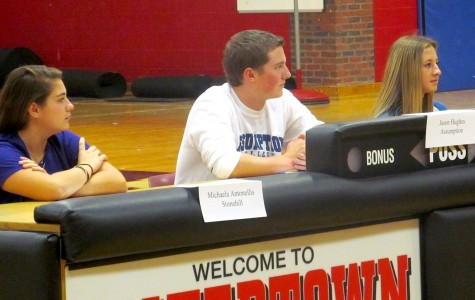 Michaela Antonellis, Jason Hughes, and Mikayala Paone (from left) listen to Watertown High athletic director Mike Lahiff during their letter of intent signing ceremony in the WHS gym on Thursday, Nov. 12, 2015.