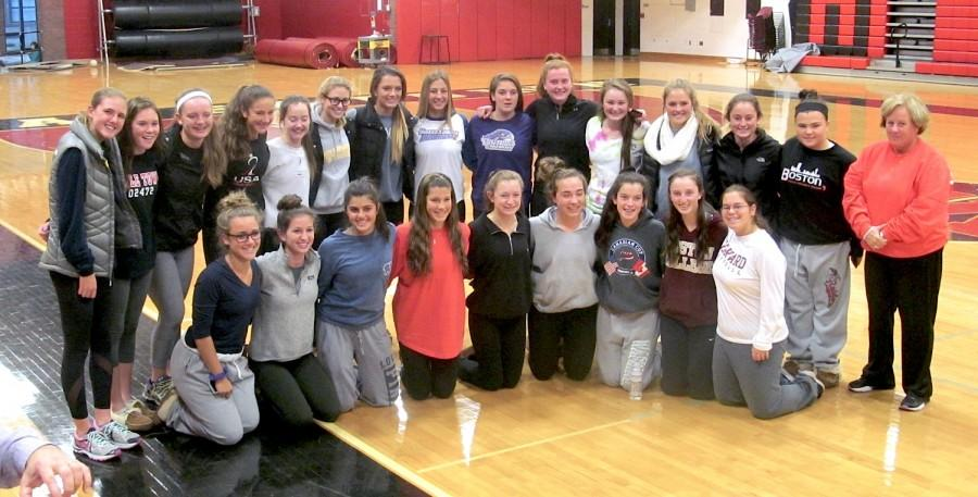 The Watertown High field hockey team -- owners of a national-record 157-game unbeaten streak -- surround Mikayla Paone and Michaela Antonellis (back row center) at their letter of intent signing ceremony in the WHS gym on Thursday, Nov. 12, 2015. Paone will be playing next year for UMass-Loweel, and Antonellis for Stonehill.