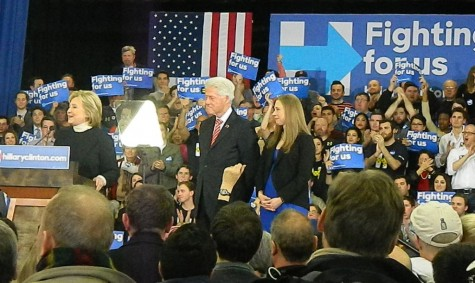 Bill Clinton and his daughter Chelsea stand on a podium at Southern New Hampshire University while presidential candidate Hillary Clinton speaks at her post-election party following the New Hampshire primary on Feb. 9, 2016.