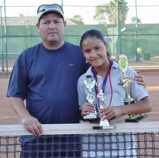 New Watertown High tennis player Lilian Marr Calderon poses with her father and some of her trophies.
