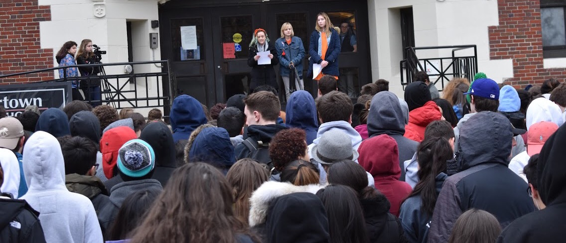 Seren Theriault (left), Olivia DeKoster (center), and Alyssa Carroll speak to students, faculty, and staff at Watertown High School during the student-led walkout March 21, 2018, to protest gun violence.