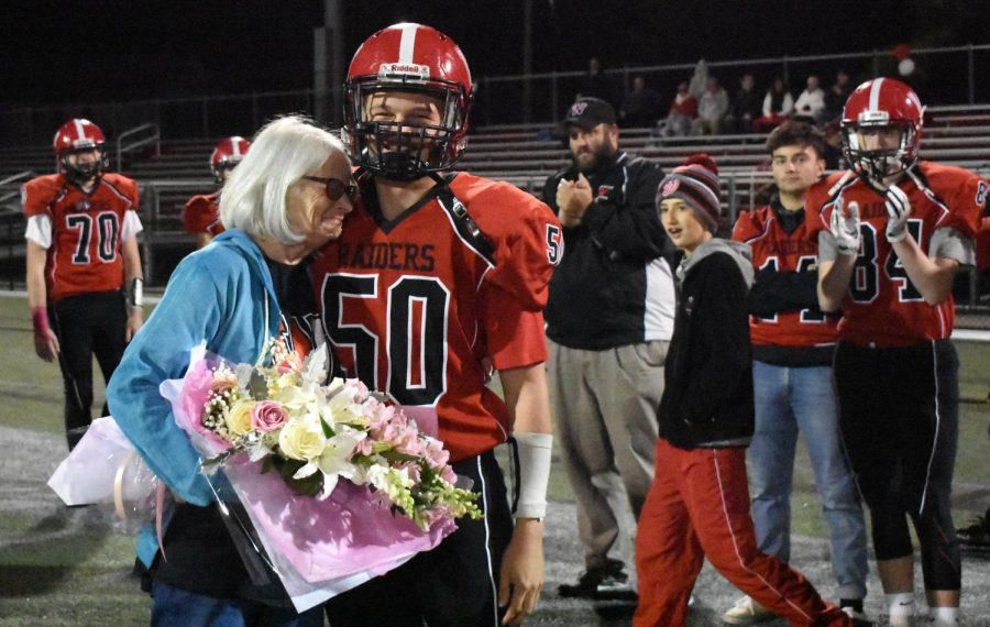 Max Bunnell (50) presents flowers to Donna Maher before the Raiders' game with Wakefield at Victory Field on Oct. 19, 2018.  Watertown High's Think Pink Week was dedicated this year to Maher, a three-time cancer survivor.