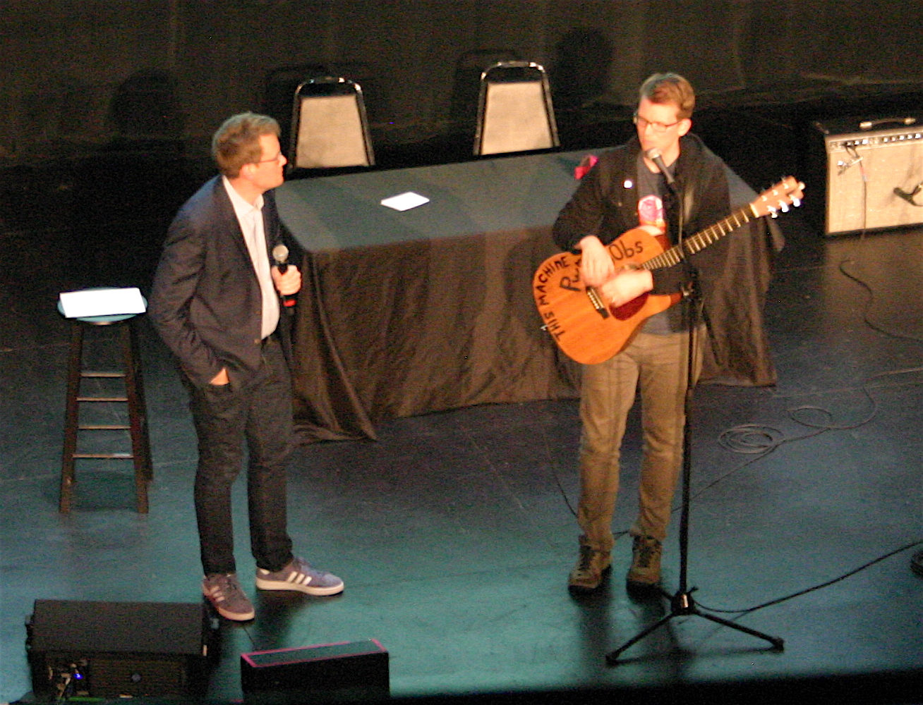 John Green (left) and brother Hank Green on stage at Boston's Wilbur Theatre on Sept. 26, 2018, as part of the promotional tour for Hank's debut book,