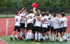 Watertown celebrates with the corner flag after the boys' soccer team defeated host Belmont, 4-1, on Saturday, Oct. 6, 2018.