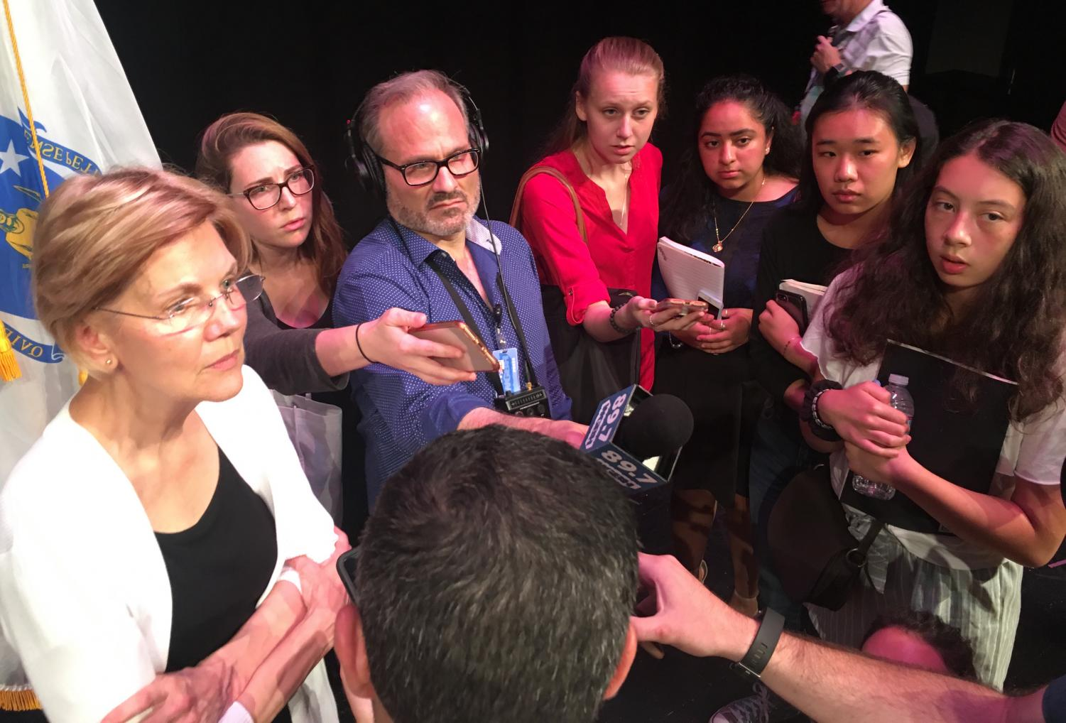 Senator Elizabeth Warren left is surrounded by reporters after a talk at Woburn High School on Aug. 8, 2018.