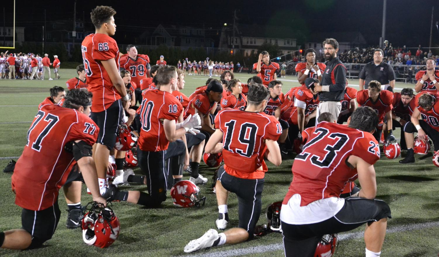 John+Cacace+and+the+Watertown+High+coaches+talk+with+the+Raiders+following+their+21-20+loss+to+undefeated+Burlington+on+Sept.+27%2C+2019%2C+at+Victory+Field.+