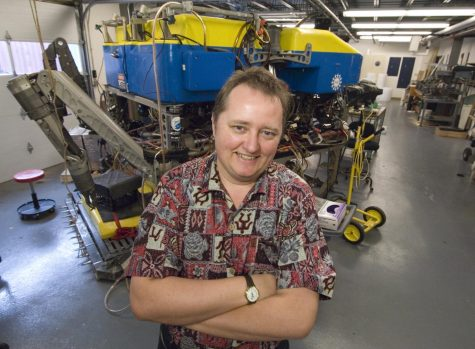 Chris German, a senior scientist at Woods Hole Oceanographic Institution (WHOI), stands in front of Jason, a remotely operated vehicle used for deep-sea exploration.