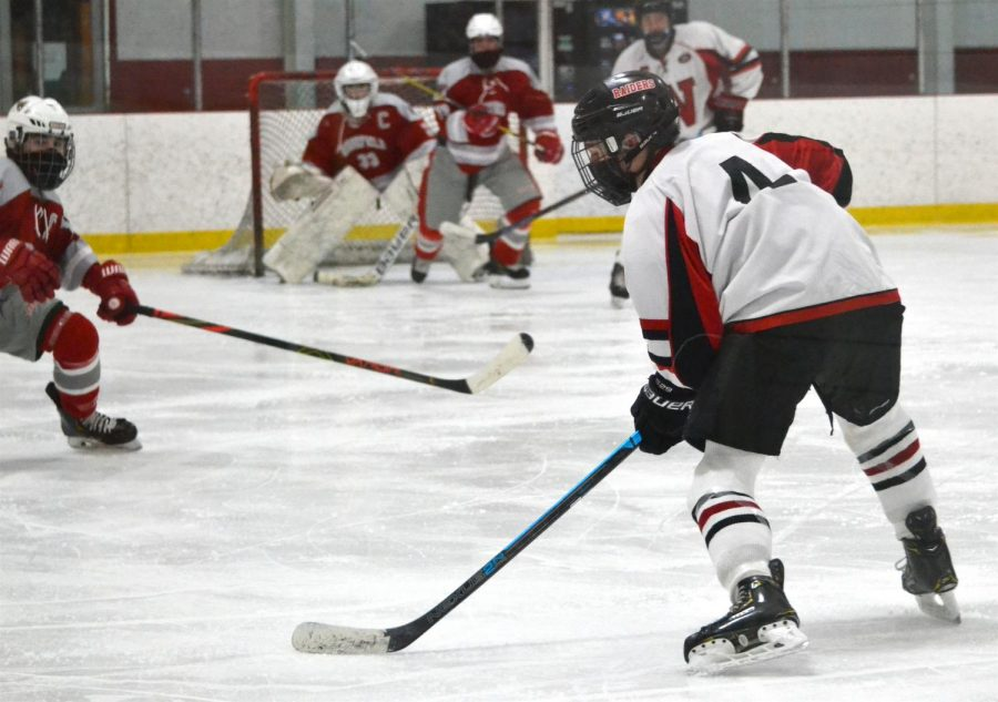 Sophomore Jack Dickie (4) lines up his shot when the Watertown High School boys' hockey team played Wakefield at John A. Ryan Arena on Friday, Jan. 15, 2021.