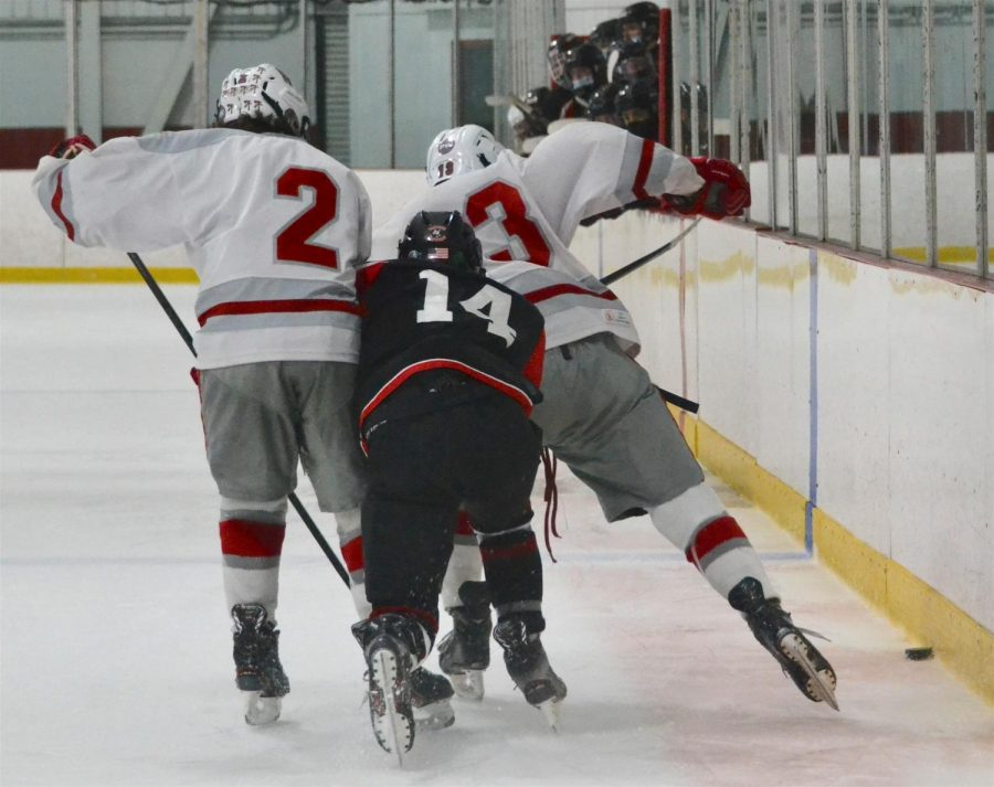Junior Michael Cormier (14) gets squeezed out during the Watertown boys' hockey game with visiting Wakefield on Feb. 3, 2021.